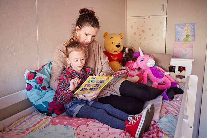 picture showing a little girl reading with her mother